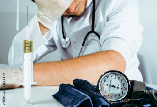 The doctor injects the drug, narcotic himself in the office Fototapeta