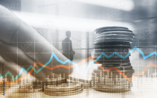 Fotografie, Obraz  Double exposure of city and rows of coins with stock and financial graph on virtual screen