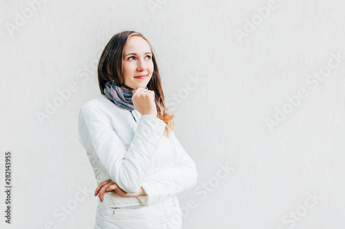 Young Caucasian brunette looks away thoughtfully touching the chin on background monochrome wall Canvas Print