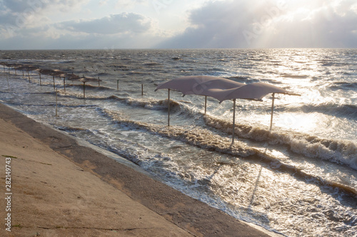 Sea waves flood the beach with umbrellas during a storm on the sea on a summer evening. Sea of Azov, Krasnodar Territory, Russia.