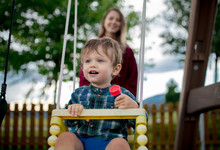 Toddler Boy Is Ride On A Swing...