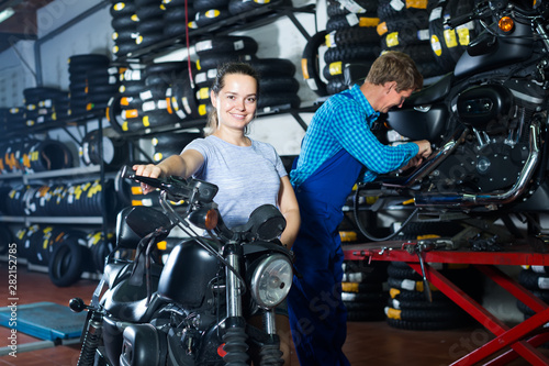 Young woman customer sitting on motorcycle