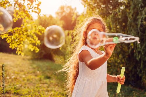 Obraz Little cute girl blowing bubbles in summer park. Kid having fun outdoors - fototapety do salonu