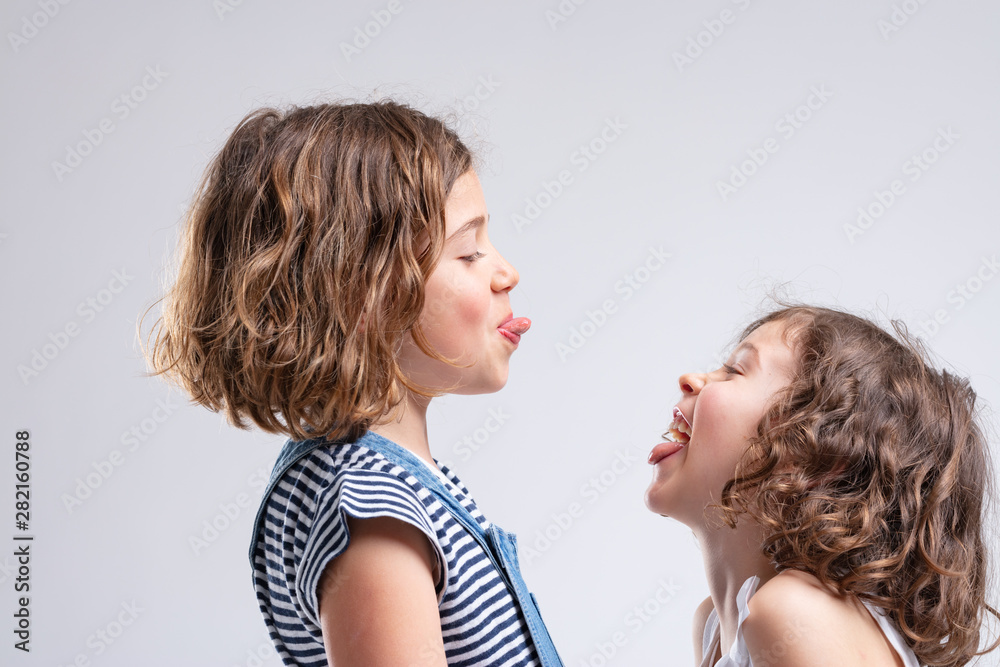 Fototapety, obrazy: Two naughty young girls sticking out their tongues