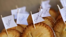 Slow Motion Shot Of A Small Box Of Different Flavored Miniature Pies. As Labeled, The Flavors Include Peach Pie, Apple Pie, And Cherry Pie. The Pies Are Being Served As Desserts At A Wedding.