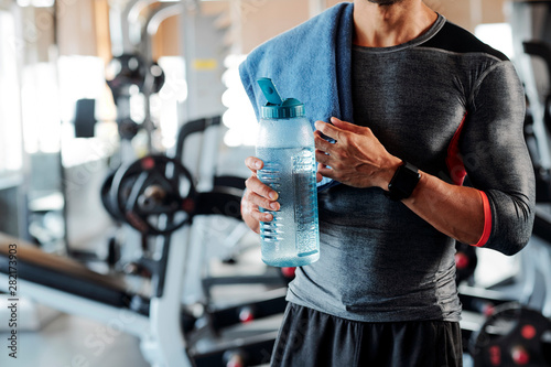 Fotografie, Obraz  Cropped image of sportsman standing with towel on his shoulder and drinking bott