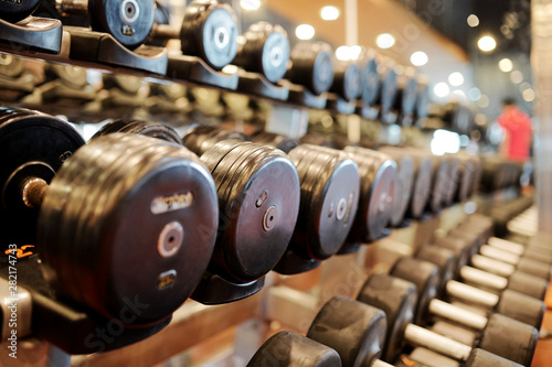 Rows of dumbbells of various weights and sizes in gym, selective focus Obraz na płótnie
