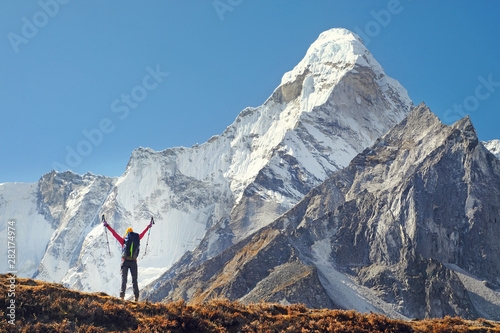 mata magnetyczna Happy woman traveler with backpack hiking in Himalayas with Ama Dablam mountain background.