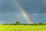 Fototapeta Tęcza - Rural landscape with rainbow in the sky after the rain.