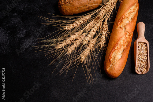 Foto op Aluminium Brood Fresh fragrant bread with grains and cones of wheat against a dark background. Assortment of baked bread on wooden table background. Fresh fragrant bread on the table. Food concept.