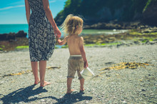 Young Mother Walking With Her Toddler On The Beach In Summer