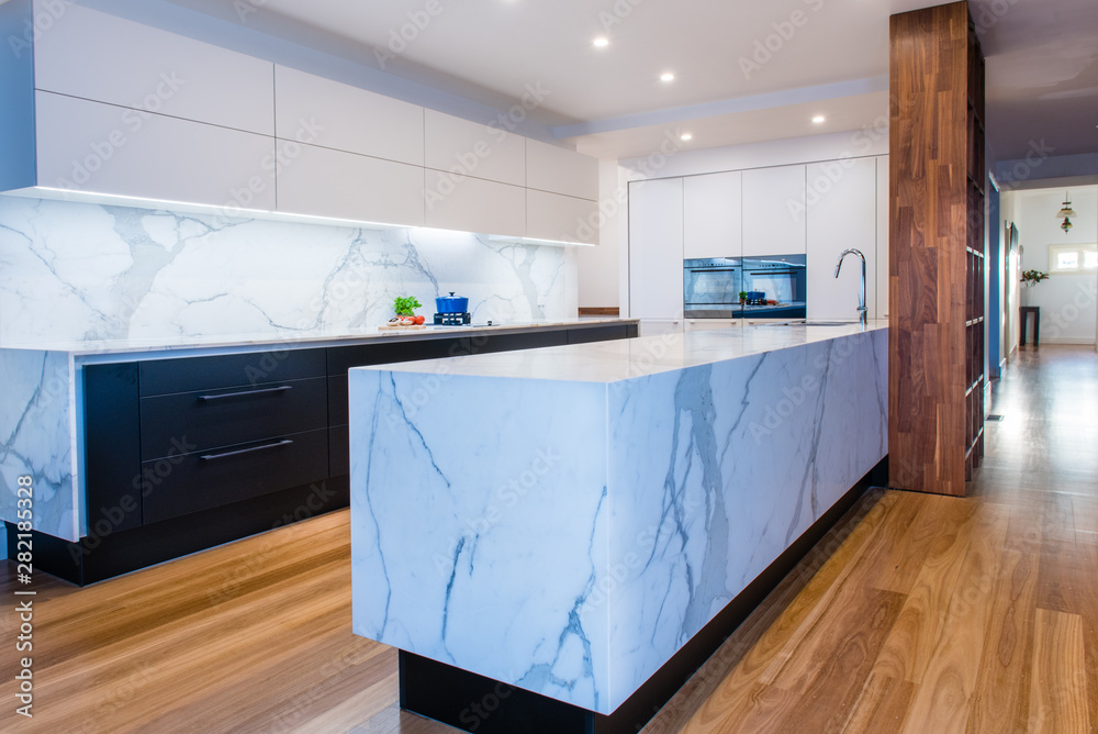 Fototapeta Modern open plan contemporary kitchen with marble island bench, countertops and back splash in Australian home