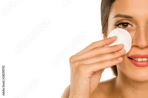 Crédence de cuisine en verre imprimé Kiev Young beautiful woman claning her face with cotton pad on white background