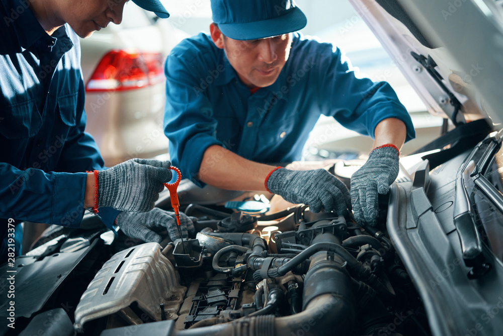 Fototapety, obrazy: Mechanic measuring level of motor oil when his coworker checking pipes