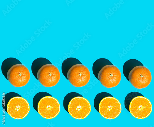 Rows of ripe juicy whole and halved orange on blue background in bright harsh sunlight with long shadow Canvas Print