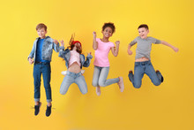 Jumping Children In Jeans Near Color Wall