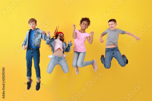Fotomural Jumping children in jeans near color wall