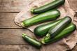 Leinwandbild Motiv Fresh zucchini squashes on wooden background