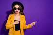 canvas print picture - Excited lady with open mouth indicating fingers empty space wear specs yellow costume isolated purple background