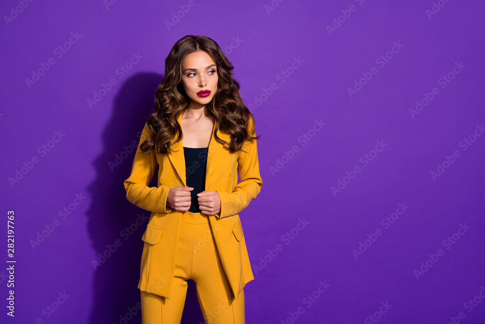 Fototapeta Photo of confident businesswoman touching her blazer while isolated with purple background