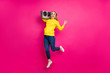 canvas print picture - Photo of jumping high with vintage tape recorder on shoulders lady wear casual outfit isolated pink background