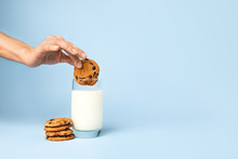 Woman Dipping Tasty Cookie In Glass Of Milk On Color Background
