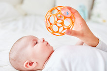 Infant Looks At Rattle Ball