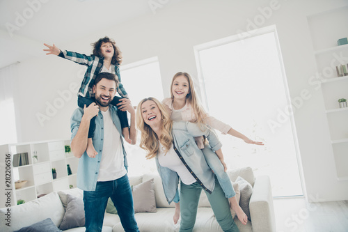 Obraz Photo of big family four members having best free time hands like wings airplane flight indoors apartments - fototapety do salonu