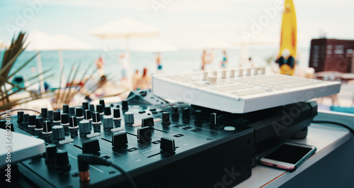 Summer music festival. Dj's sound equipment and people on blurred background.  Shallow depth of field - 282208118
