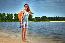 Pretty Young Woman With Backpack On Riverside Beach