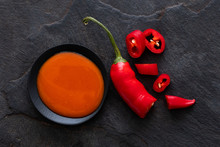 Peri Peri Chilli Sauce In A Black Ceramic Bowl Next To A Cut Up Chilli Pepper Isolated On Black Slate From Above.
