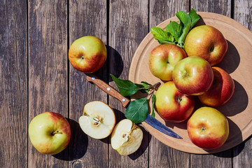 Fresh red apples with green leaves on a wooden old table. On a wooden background with sliced apple. Free space for text. soft focus