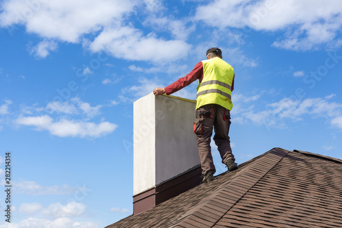 Fotografija Man measuring chimney on roof top of new house under construction