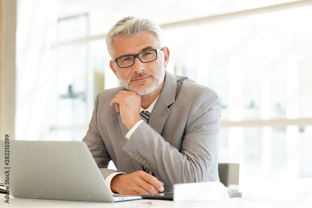 Fototapeta Mature businessman sitting at desk looking at camera