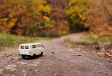 White Little Toy Car Rides On The Road Against The Background Of Autumn Yellow Trees. Place For Text, Design Blank, Copy Space, Hello Autumn.