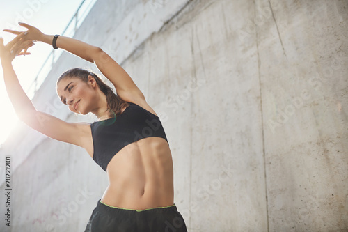 Low-angle shot pleased, motivated sporty fitness woman in sportsbra and shorts, lift hands up stretching, do morning exercise, warm-up body before marathon, smiling stand concrete wall on street - 282219101