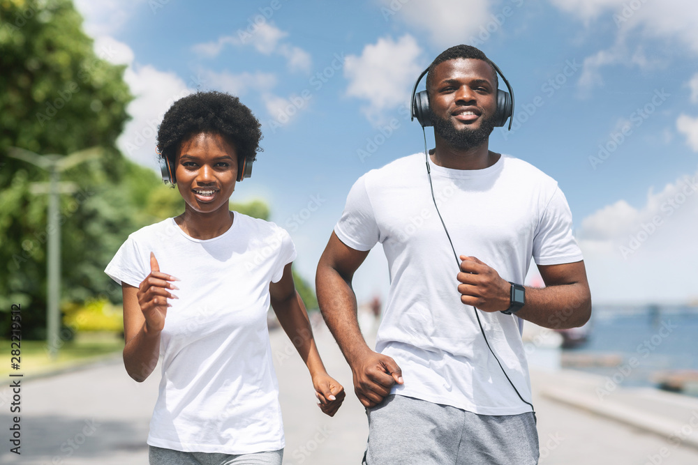 Fototapety, obrazy: Smiling African American Couple Jogging Along River Bank In Morning