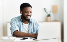 Smiling African-american Guy In Earphones Studying Foreign Language Online