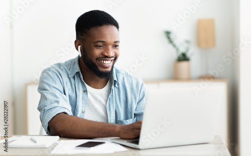 Foto Smiling african-american guy in earphones studying foreign language online