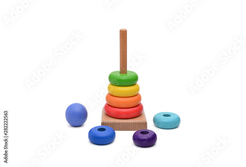 Toy pyramid from rainbow colored wooden rings with a ball head on top. Toy for babies to joyfully learn mechanical skills and colors. Studio shot. Isolated on white background
