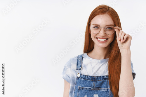 Cuadros en Lienzo  Cheerful smiling redhead, young girl grinning confident checking transparent gla
