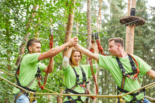 Young People In The High Ropes Course Celebrate Teamwork