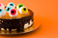 Halloween Cake With Candy Eyes Decoration On Orange Background. Copyspace