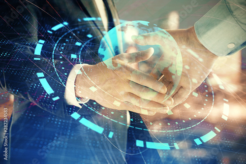Fotomural  Double exposure of world map on cityscape background with two businessmen handshake