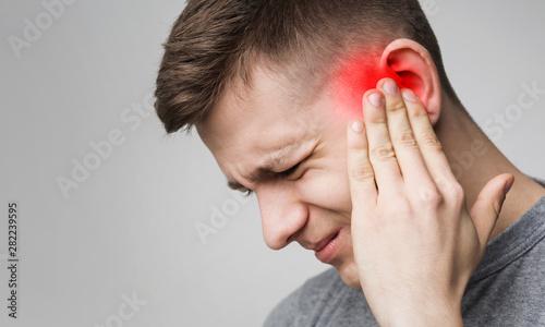 Young man has sore ear, suffering from otitis Billede på lærred