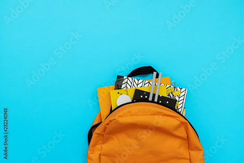 Obraz Back to school concept. Backpack with school supplies on blue background. Top view. Copy space. Flat lay - fototapety do salonu