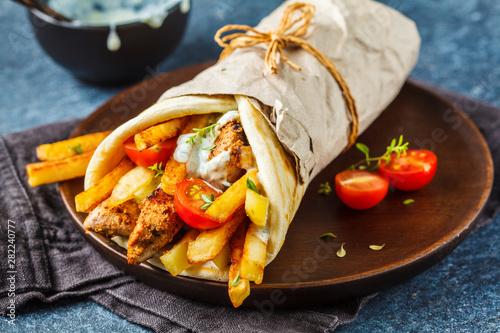 Photo  Gyros souvlaki wraps in pita bread with chicken, potatoes and tzatziki sauce