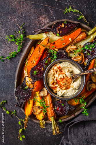Baked vegetables with hummus in a dark dish, top view. Canvas Print
