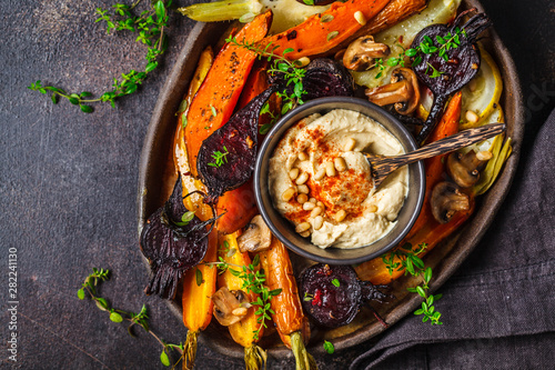 Fototapeta Baked vegetables with hummus in a dark dish, top view. obraz