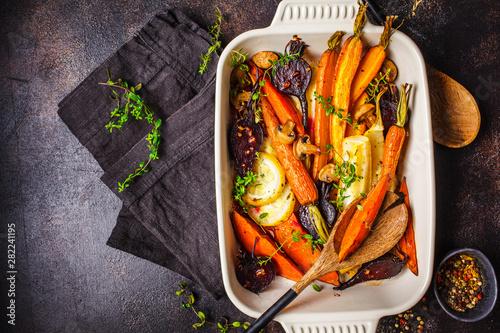 Fototapeta Baked vegetables with thyme in the oven dish, dark background. obraz